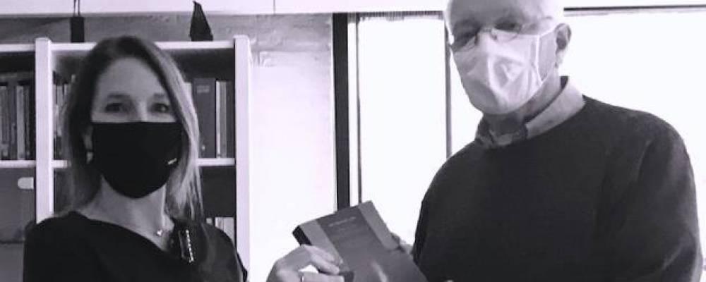 Arie Knuistingh Neven overhandigt een exemplaar van zijn nieuwe boek aan zijn dochter Floor